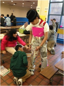 A corps member prepares to model his students' fashion creation.